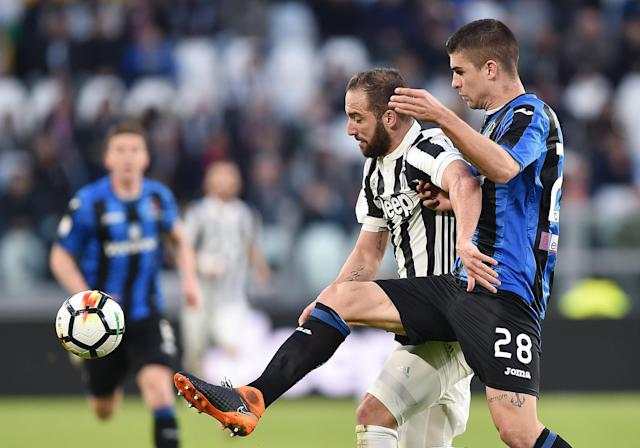 Juventus' Gonzalo Higuain, left, and Atalanta's Gianluca Mancini vie for the ball during the Italian Serie A soccer match between Juventus and Atalanta at the Allianz Stadium in Turin, Italy, Wednesday, March 14, 2018. (Alessandro Di Marco/ANSA via AP)