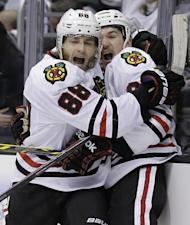 Patrick Kane, left, celebrates his tie-breaking goal with center Andrew Shaw. (AP)