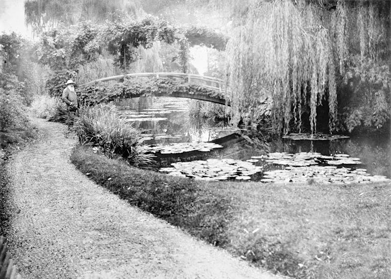 This photo provided by the New York Botanical Garden shows French impressionist artist Claude Monet in his garden in Giverny, France. Monet once said he owed becoming a painter to his love for flowers and a new exhibit at the New York Botanical Garden explores his passion for his beloved water lilies, irises and gardens and how they influenced his art. (AP Photo/New York Botanical Garden)