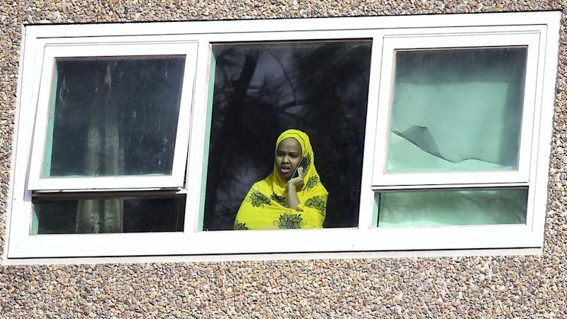 A woman in a window on a mobile phone