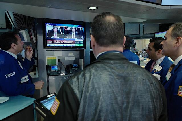 <p>Stock traders at the New York Stock Exchange watch former FBI Director James Comey on a television monitor, June 8, 2017, as he testifies before a congressional committee in Washington. (Mark Lennihan/AP) </p>