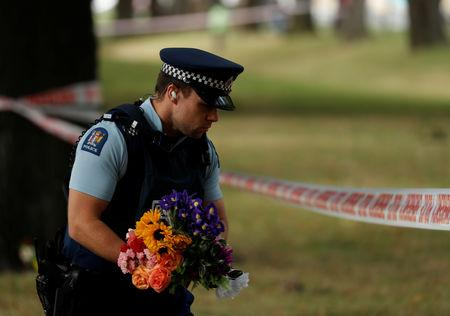 A police officer holds flowers near a police line outside Masjid Al Noor mosque in Christchurch, New Zealand, March 17, 2019. REUTERS/Jorge Silva