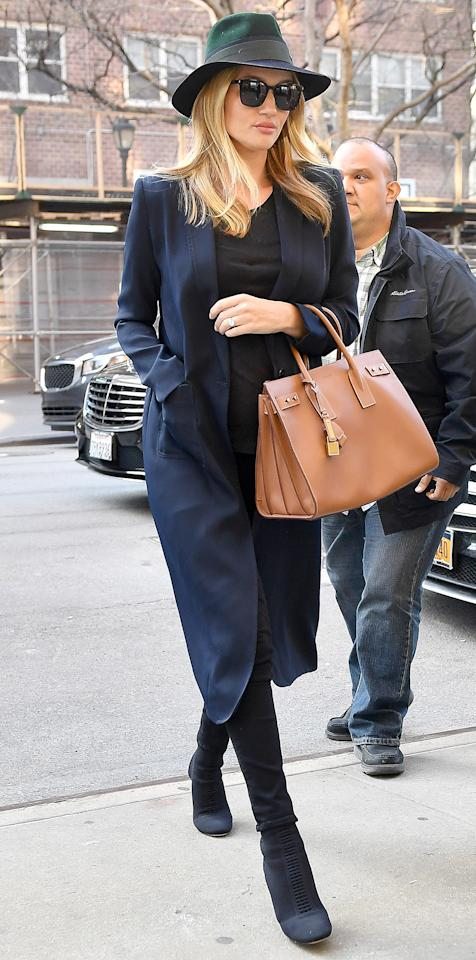 <p>The pregnant model looked put-together for an outing with Jason Statham in a navy coat, black top, and over-the-knee suede boots. Huntington-Whiteley polished off the look with a brown leather purse, and green and blue hat for a cloudy day out in N.Y.C.</p>