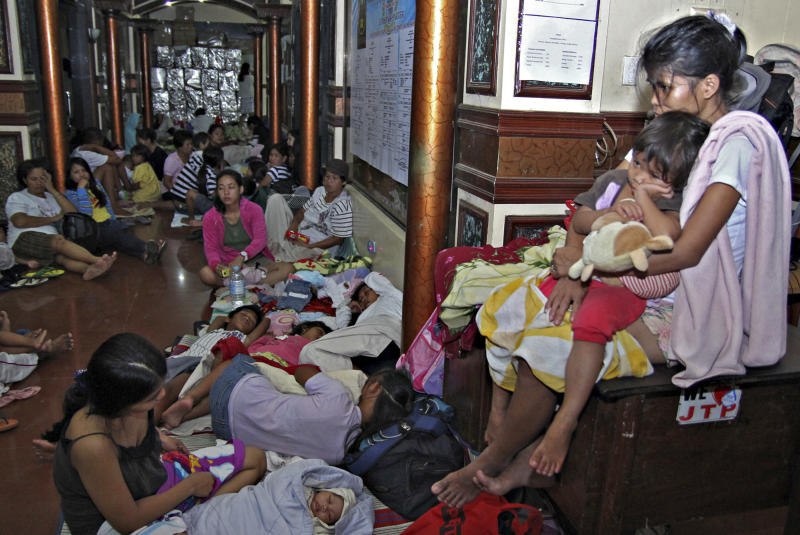 Residents take shelter at the lobby of the city hall in Tandag, Surigao Del Sur province in southern Philippines, Friday, Aug. 31, 2012, following a 7.6 magnitude earthquake that struck eastern and southern Philippines. The quake set off car alarms, shook items off shelves and sent many coastal residents fleeing for high ground before the Pacific Tsunami Warning Center lifted all tsunami alerts it had issued for the Philippines and neighboring countries from Indonesia to Japan, and for Pacific islands as far away as the Northern Marianas. (AP Photo/Erwin Mascarinas)