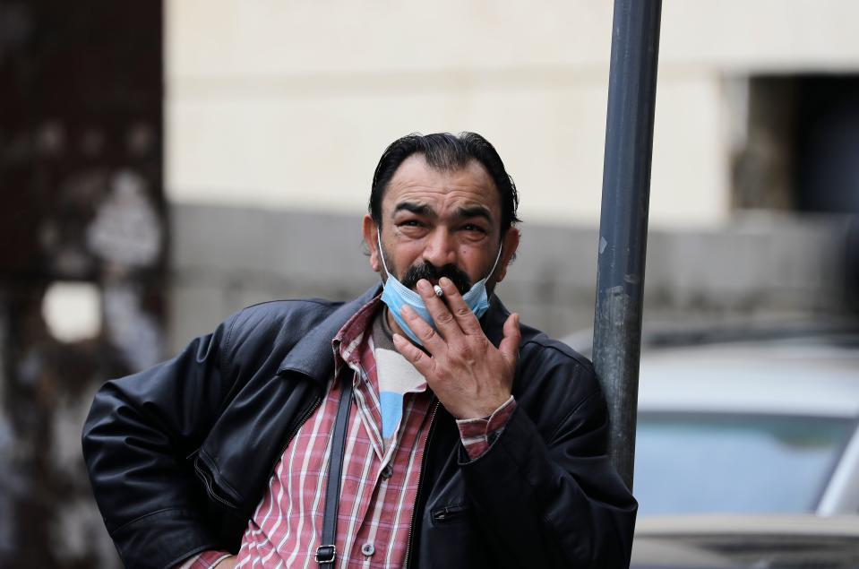 A Lebanese man smokes a cigarette as he wears a protective mask at a street in Beirut on March 12, 2020. - Lebanon yesterday suspended flights from countries hit hardest by the novel coronavirus after announcing its second death from the pandemic in two days. The Mediterranean nation has recorded at least 61 cases of COVID-19. Prime Minister Hassan Diab said Lebanon would suspend all trips to and from Italy, South Korea, Iran and China, the hardest hit countries. (Photo by JOSEPH EID / AFP) (Photo by JOSEPH EID/AFP via Getty Images)