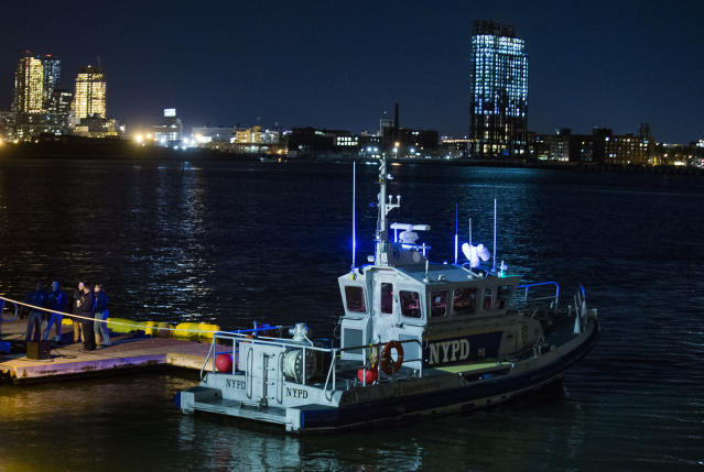 <p>Yellow buoys that a New York police officer said are suspending a helicopter that crashed on the East River float next to a NYPD police boat at a pier in New York on March 11, 2018. (Photo: Andres Kudacki/AP) </p>