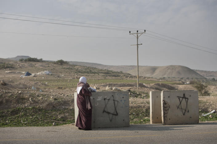 A Palestinian woman waits for transportation near Settlement of Mehola in the Jordan Valley, a strip of West Bank land along the border with Jordan, Thursday, Jan. 2, 2014. A senior Israeli Cabinet minister and more than a dozen hawkish legislators poured cement at a construction site in a settlement in the West Bank's Jordan Valley on Thursday, in what they said was a message to visiting U.S. Secretary of State John Kerry that Israel will never relinquish the strategic area. (AP Photo/Oded Balilty)