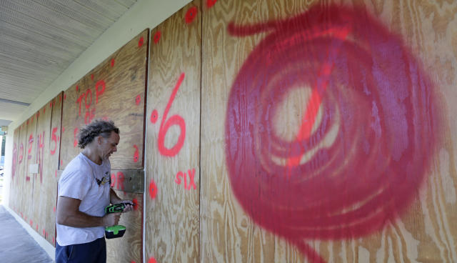 <p>Erik Budman drills a nail into the plywood as he prepares for Hurricane Irma, at a local business, Tuesday, Sept. 5, 2017, in Key Largo, Fla. (Photo: Alan Diaz/AP) </p>