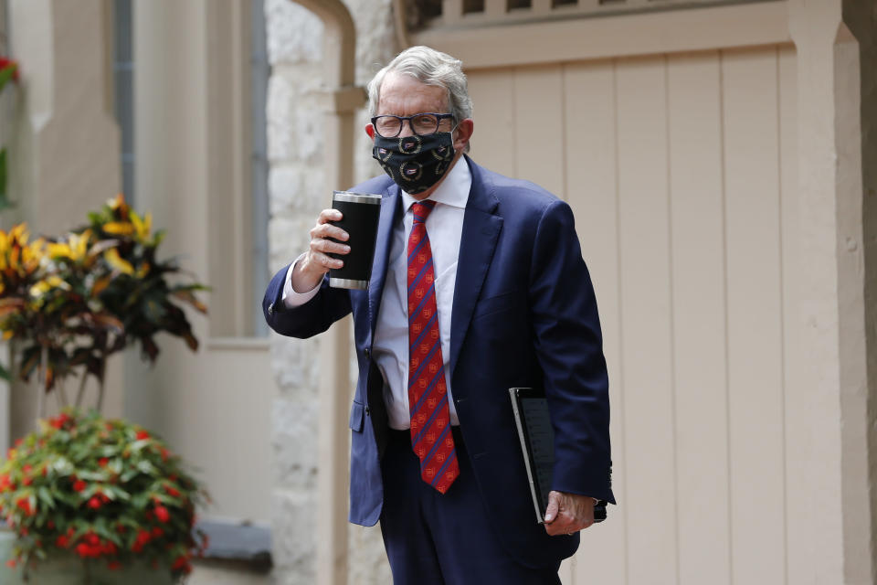 Ohio Gov. Mike DeWine acknowledges members of the media while entering his residence after testing positive for COVID-19 earlier in the day Thursday, Aug. 6, 2020, in Bexley, Ohio. (AP Photo/Jay LaPrete)