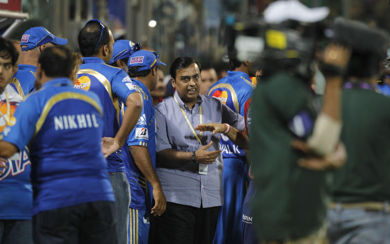 Mumbai Indians' co-owner Mukesh Ambani, center, mingles with players as his team wins during an Indian Premier League cricket match against Delhi Daredevils in New Delhi, India, Sunday, April 10, 2011. The fourth edition of the world's richest cricket tournament scheduled between April 8-May 28 comprises of 10 teams and 74 matches. (AP Photo/Saurabh Das)