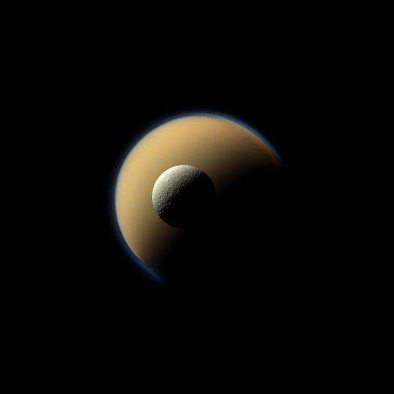Saturn's largest and second largest moons, Titan and Rhea, appear to be stacked on top of each other in this true-color scene from NASA's Cassini spacecraft released on Dec. 23, 2013. The north polar hood can be seen on Titan appearing as a det