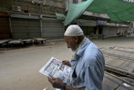A man reads a copy of morning news paper at a market closed due to strikes called by the the country's religious political parties over the security forces's crackdown against a banned Tehreek-e-Labaik Pakistan party, in Karachi, Pakistan, Monday, April 19, 2021. An outlawed Pakistani Islamist political group freed 11 policemen almost a day after taking them hostage in the eastern city of Lahore amid violent clashes with security forces, the country's interior minister said Monday. (AP Photo/Fareed Khan)