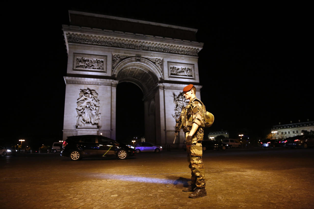 A soldier stands guard near the Arc of Thriomphe at the top of the Champs Elysees avenue in Paris, after a fatal shooting in which a police officer was killed along with an attacker, Thursday, April 20, 2017. French media are reporting that two police officers were shot Thursday on the famed shopping boulevard. Many police vehicles can be seen on the avenue that passes many of the city's most iconic landmarks. (AP Photo/Kamil Zihnioglu)