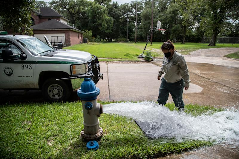 A Lake Jackson water waste operator flushes water from a fire hydrant on Monday in Lake Jackson, Texas, after a brain-eating amoeba was discovered in the city's water supply. (Photo: ASSOCIATED PRESS)