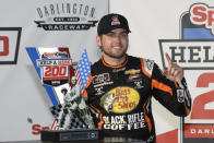 Noah Gragson stands with the trophy after winning a NASCAR Xfinity Series auto race Saturday, Sept. 4, 2021, in Darlington, S.C. (AP Photo/John Amis)