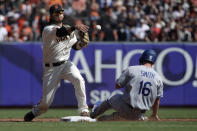 San Francisco Giants shortstop Brandon Crawford, left, throws to first base after forcing Los Angeles Dodgers' Will Smith (16) out at second base during the third inning of a baseball game in San Francisco, Sunday, Sept. 29, 2019. (AP Photo/Jeff Chiu)