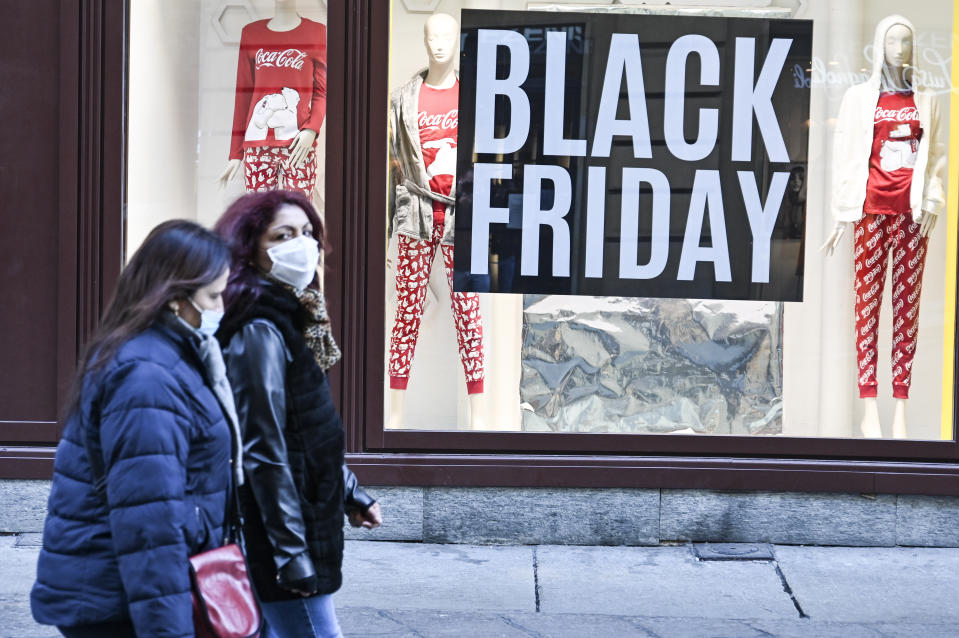 "TURIN, ITALY - NOVEMBER 24: Passers-by in protective masks walk past a shop with ""Black Friday"" signs on a central street in Turin on November 24, 2020 in Turin, Italy. While the whole country is in lockdown of varying degrees between regions, the contagions seems to be dropping.  (Photo by Diego Puletto/Getty Images)"