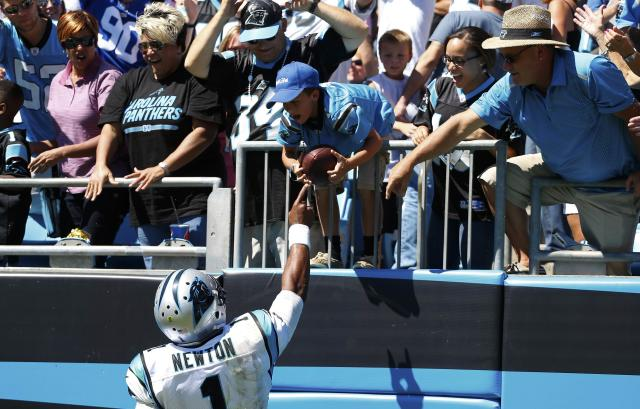 Carolina Panthers quarterback Cam Newton (1) hands a game ball to a fan after a touchdown against the New York Giants during an NFL football game in Charlotte, North Carolina September 22, 2013. REUTERS/Chris Keane (UNITED STATES - Tags: SPORT FOOTBALL)