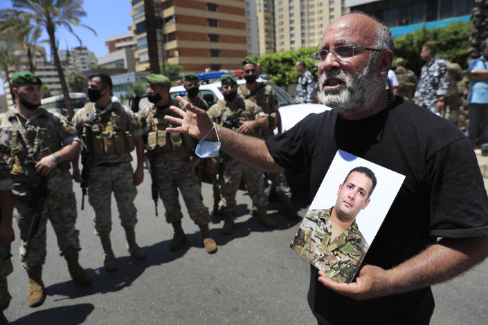 A father of a Lebanese army soldier who killed during the last year's massive blast at Beirut's seaport, holds his son's portrait and shouts slogans during a protest near the tightly-secured residents of parliament speaker Nabih Berri, in Beirut, Lebanon, Friday, July 9, 2021. The protest came after last week's decision by the judge to pursue senior politicians and former and current security chiefs in the case, and requested permission for their prosecution. (AP Photo/Hussein Malla)