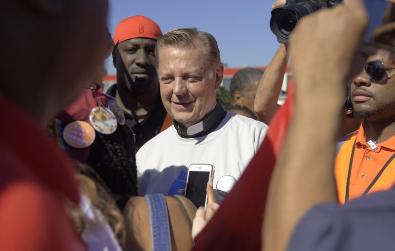 The Rev. Michael Pfleger speaks to protesters before marching on the Dan Ryan Expressway, Saturday, July 7, 2018, in Chicago. The protesters shut down the expressway to draw attention to the city's gun violence and pressure public officials to do more to help neighborhoods hardest hit by it.(AP Photo/Annie Rice)