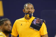 FILE - Michigan head coach Juwan Howard has a towel honoring former Georgetown head coach John Thompson on his shoulder in the second half of an NCAA college basketball game against Rutgers in Ann Arbor, Mich., in this Thursday, Feb. 18, 2021, file photo. Michigan coach Juwan Howard was honored as The Associated Press men's basketball coach of the year Thursday, April 1, 2021. (AP Photo/Paul Sancya, File)