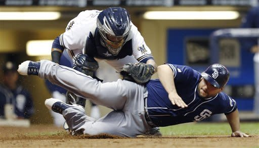 San Diego Padres' Yonder Alonso is tagged out at home by Milwaukee Brewers' Martin Maldonado during the sixth inning of a baseball game Tuesday, Oct. 2, 2012, in Milwaukee. (AP Photo/Tom Lynn)