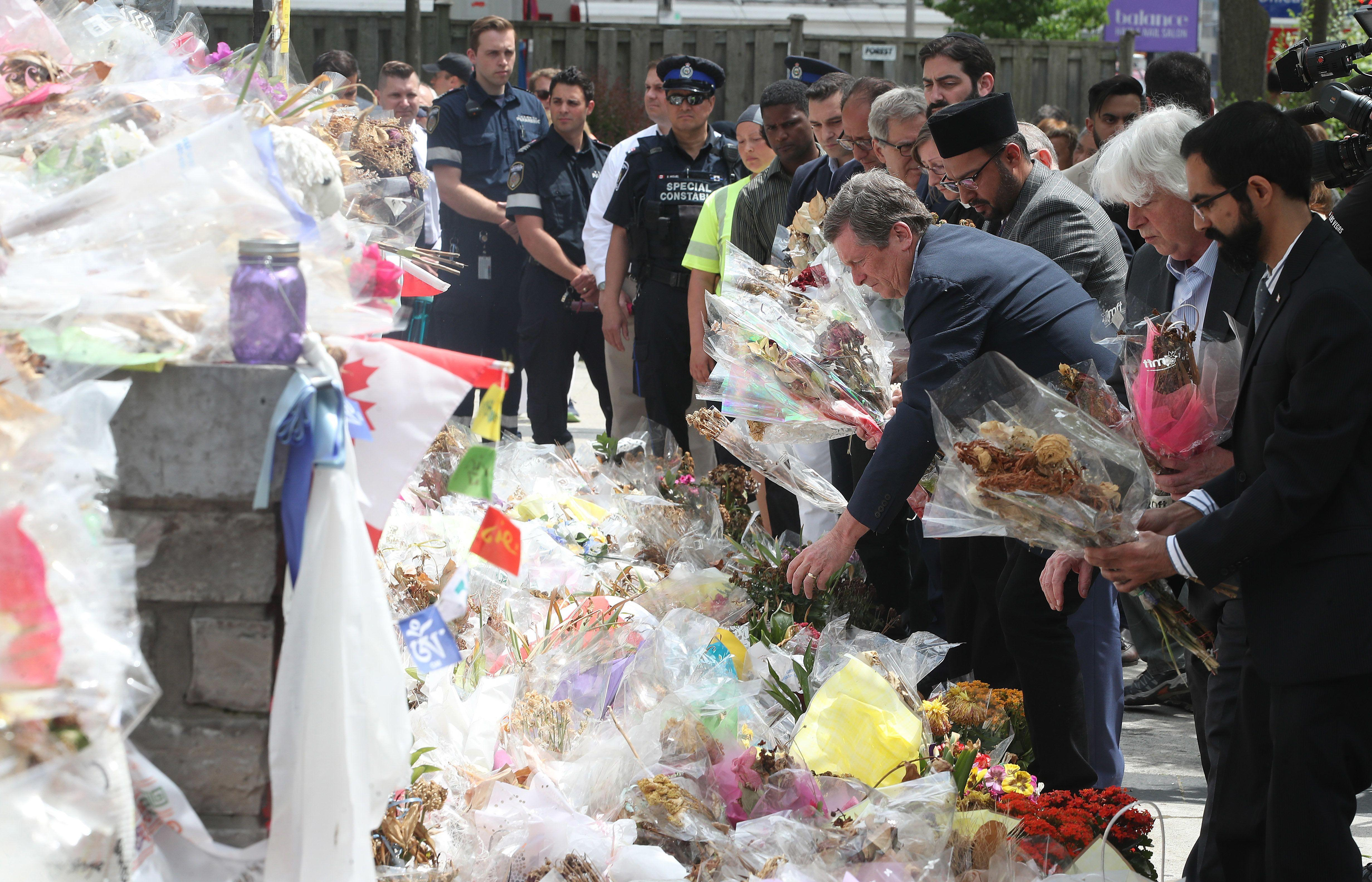 TORONTO, ON- JUNE 3 - Toronto Mayor John Tory picks u flowers along with religious leaders, first responders and people affected came out to decommission the memorials to the 10 people killed in the Yonge Street van attack. at in Toronto. June 3, 2018. (Steve Russell/Toronto Star via Getty Images)