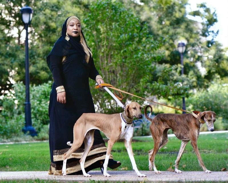 Aliya Taylor walks with two Azawakh, a rare breed of sighthound from Africa, while wearing a black abaya. (Photo: Terri Hirsch)