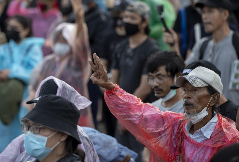 A pro-democracy protester raises a three-fingers, symbol of resistance salute during a rally at Sanam Luang in Bangkok, Thailand, Sunday, Sept. 20, 2020. Thousands of demonstrators who occupied a historic field in Thailand's capital overnight continued with their rally on Sunday to support the demands of a student-led protest movement for new elections and reform of the monarchy. (AP Photo/Gemunu Amarasinghe)