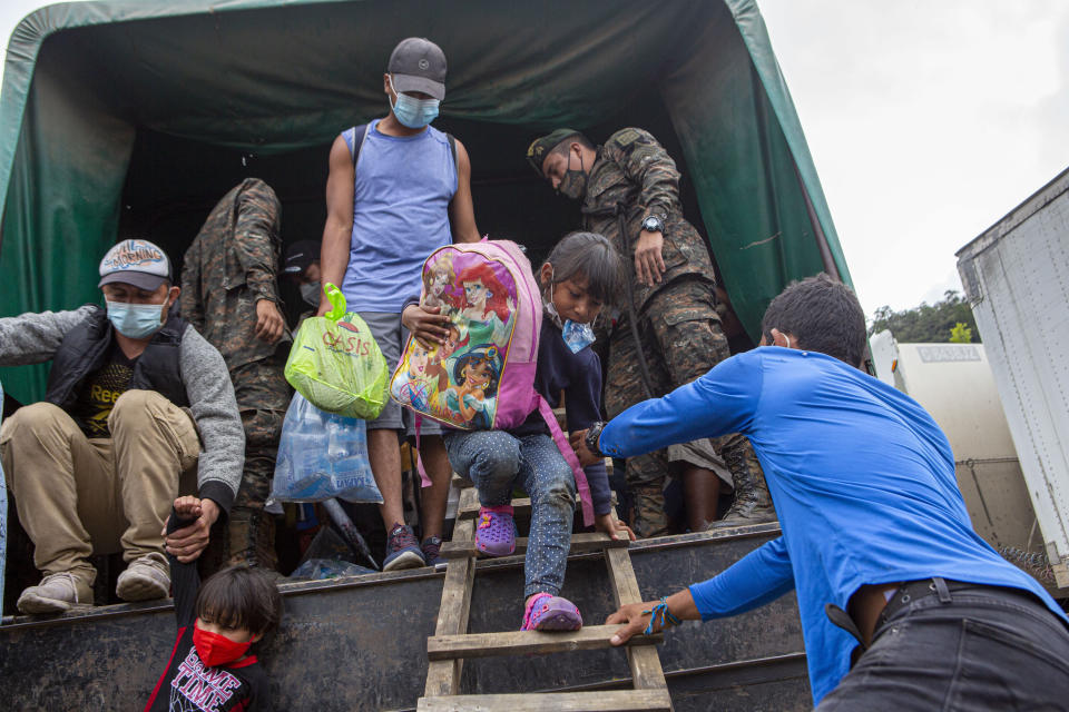 A Honduran migrant child is helped off a Guatemalan army truck after being returned to El Florido, Guatemala, one of the border points between Guatemala and Honduras, Tuesday, Jan. 19, 2021. In January, Guatemalan authorities blocked the year's first caravan, sending nearly 5,000 Hondurans back to their country over a 10-day span. (AP Photo/Oliver de Ros)