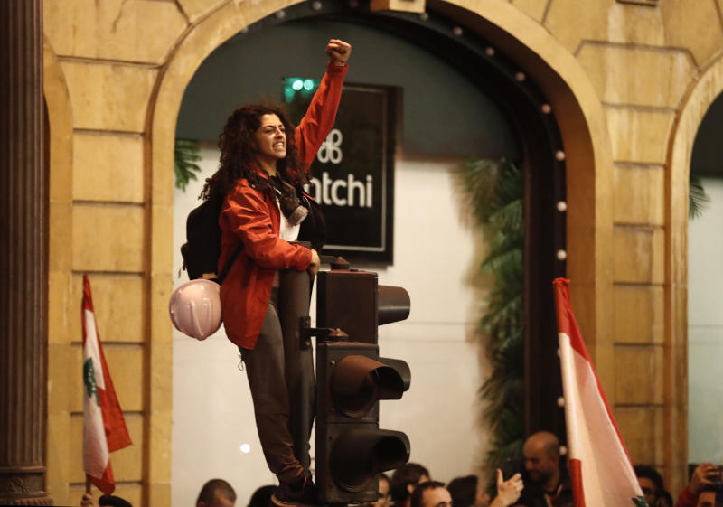 An anti-government protesters stands on a traffic light, as she shouts slogans during a protest near the parliament square, in downtown Beirut, Lebanon, Sunday, Dec. 15, 2019. Lebanese security forces fired tear gas, rubber bullets and water cannons Sunday to disperse hundreds of protesters for a second straight day, ending what started as a peaceful rally in defiance of the toughest crackdown on anti-government demonstrations in two months. (AP Photo/Hussein Malla)
