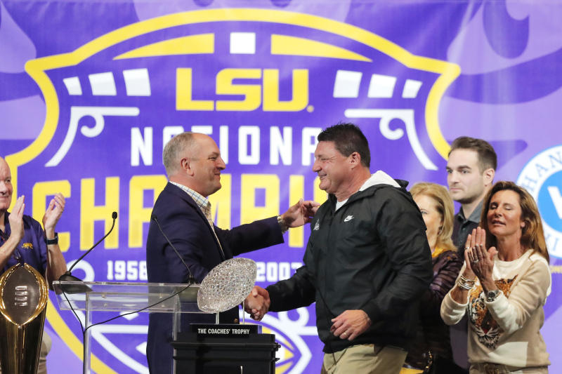 LSU head coach Ed Orgeron, right, is greeted by Louisiana Gov. John Bel Edwards during a celebration of their NCAA college football championship, Saturday, Jan. 18, 2020, on the LSU campus in Baton Rouge, La. (AP Photo/Gerald Herbert)