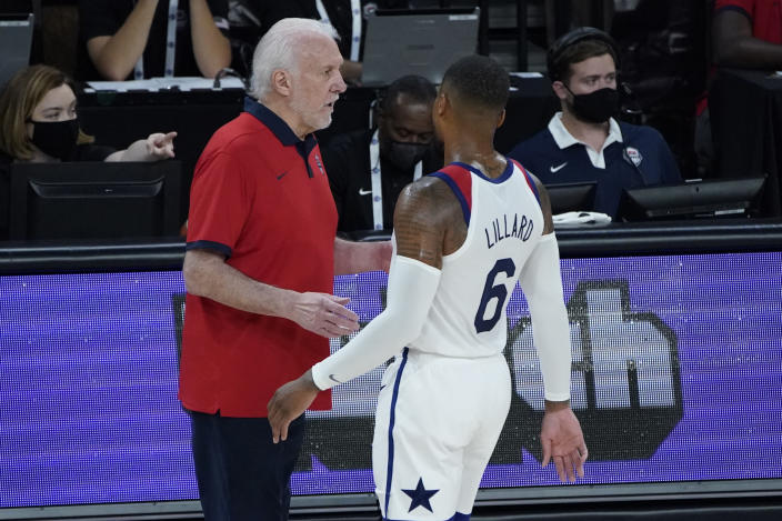 United States head coach Gregg Popovich speaks with Damian Lillard (6) during the first half of an exhibition basketball game against Spain in preparation for the Olympics, Sunday, July 18, 2021, in Las Vegas. (AP Photo/John Locher)
