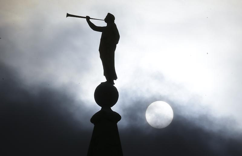 """FILE - In this Jan. 29, 2013, file photo, the angel Moroni statue, silhouetted against a cloud-covered sky, sits atop the Salt Lake Temple in Temple Square in Salt Lake City. A newly-posted article, part of a series of recent online articles posted on the website of The Church of Jesus Christ of Latter-day Saints, affirms the faith's belief that humans can become like God in eternity, but explains that the """"cartoonish image of people receiving their own planets"""" is not how the religion envisions it. (AP Photo/Rick Bowmer, File)"""