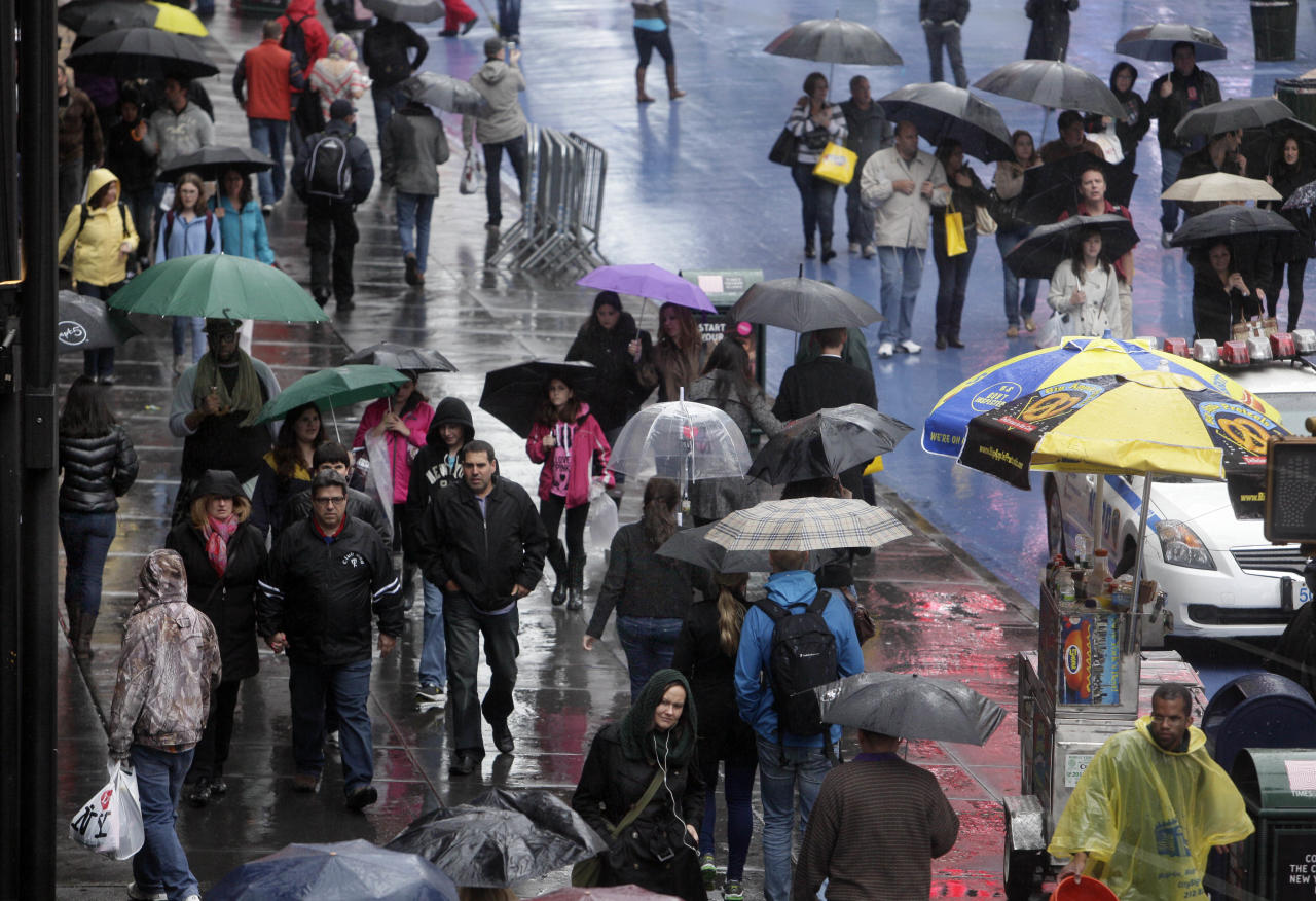 People walk through New York's Times Square, Sunday, April 22, 2012. A spring nor'easter is hitting the East Coast on Sunday and is expected to bring rain and heavy winds and even snow in some places as it strengthens into early Monday, a punctuation to a relatively dry stretch of weather for the Northeast. (AP Photo/Richard Drew)