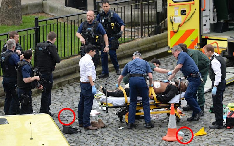The Westminster attacker on a stretcher being treated by paramedics, with two knives lying on the ground - Credit: Stefan Rousseau/PA