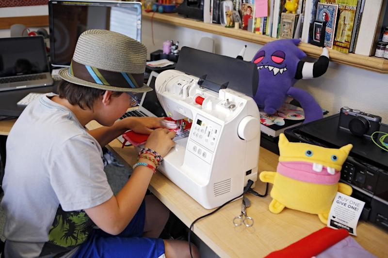This photo taken on May 23, 2013 shows Ben Tollison sewing a monster doll at his home in Fort Collins, Colo. The Tollison family launched Monster to Love, a company that makes plush monster toys. (AP Photo/Ed Andrieski)
