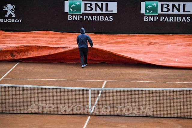 Rain pain: A worker covers the court in Rome during the men's final on Sunday (AFP Photo/Andreas SOLARO)