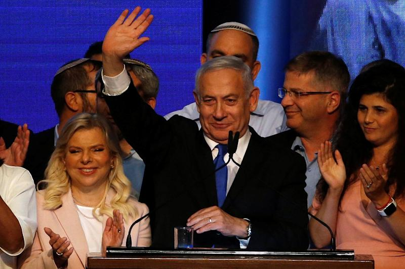 Israeli Prime Minister Benjamin Netanyahu stands next to his wife Sara as he waves to supporters at his Likud party headquarters following the announcement of exit polls. (REUTERS)