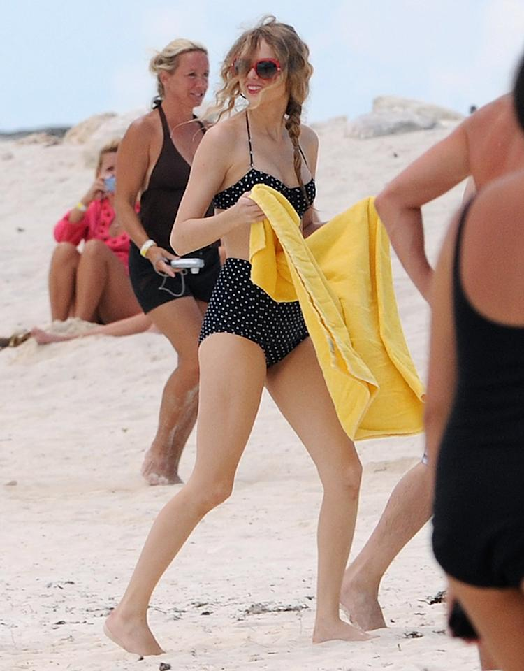 "Taylor looked ""wonderstruck"" in her classic 1940s-style bikini as she frolicked at the Atlantis Resort in the Bahamas. We love that she let her curls go au naturale and finished off her seaside style with a pair of big red sunglasses. The thin strap on her suit — as opposed to her typical thick-strapped halter — accentuates her fabulous neckline as well. What a bathing beauty! (6/19/2010)<br /><br /><br />"
