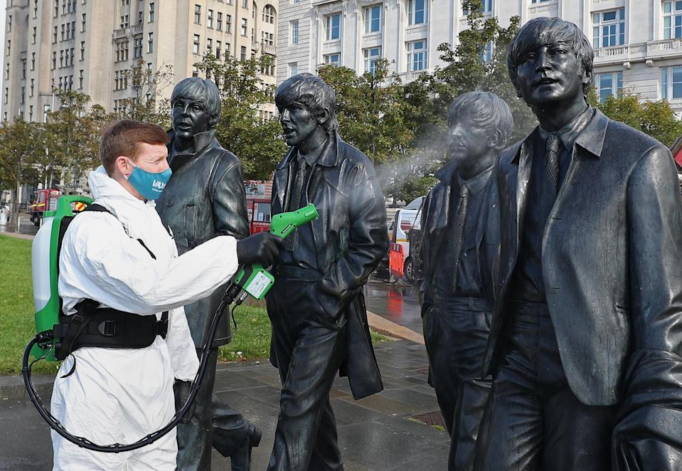 A worker spray cleans the Beatles statue in Liverpool.