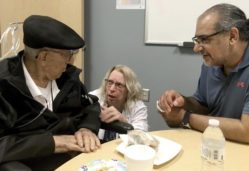 The Rev. John Sabbagh, left, and his son Ebby Sabbagh talk with nurse practitioner Kim O'Riley, Friday, Sept. 7, 2018 in Gilbert, Ariz. Thirty-five years after John Sabbagh cared for his son when he was shot in their native Lebanon, Ebby is returning that devotion. Both the Rev. John Ibraham Sabbagh and 54-year-old son, Ebby Sabbagh, are celebrating one year of going strong since the elder Sabbagh received a crucial stem-cell transplant. (AP Photo/Terry Tang)