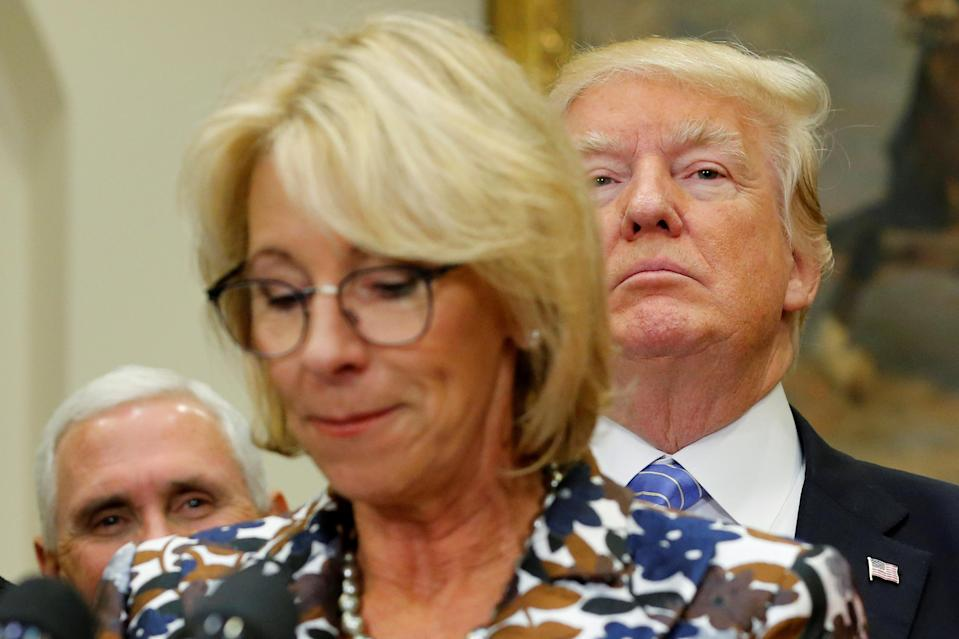 U.S. President Donald Trump (R, background) and Vice President Mike Pence (L) wait to interrupt Education Secretary Betsy DeVos as she speaks to students at a school choice event at the White House in Washington, U.S. May 3, 2017. (Photo: REUTERS/Jonathan Ernst)