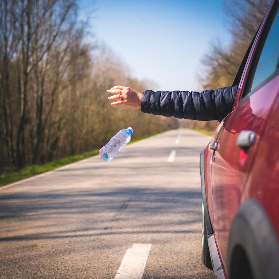 Driver of car throwing bottle out of window. Source: Getty Images
