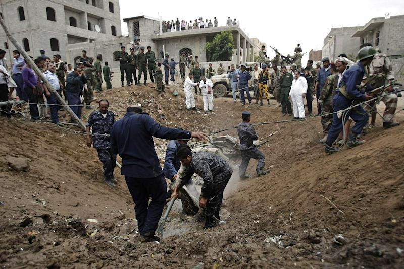 Yemeni security forces and soldiers inspect the site of a plane crash in Sanaa, Yemen, Monday, May 13, 2013. A Yemeni military plane on a training exercise crashed Monday in the country's capital, slamming into a residential neighborhood and setting at least four houses ablaze. (AP Photo/Hani Mohammed)