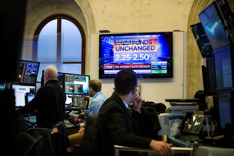 Traders watch a television broadcasting a Federal Reserve announcement on the floor of the New York Stock Exchange (NYSE) in New York, U.S., on Wednesday, Jan. 30, 2019. U.S. stocks surged and the dollar tumbled after the Federal Reserve signaled a stark dovish turn in its latest policy statement. Photographer: Michael Nagle/Bloomberg via Getty Images