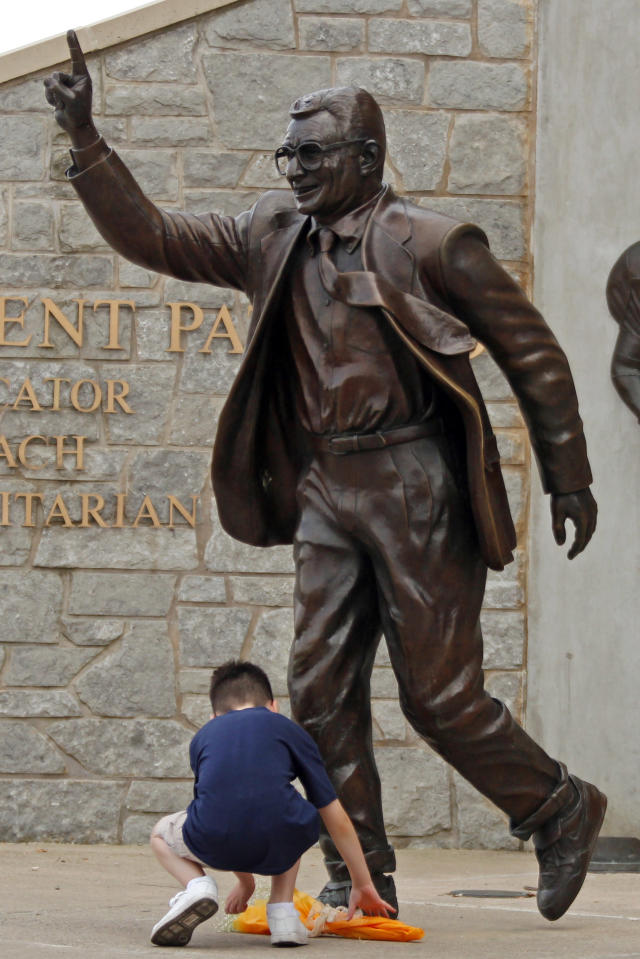 A young boy places a yellow rose at the foot of a statue of former Penn State head football coach Joe Paterno outside Beaver Stadium in State College, Pa., Thursday, July 12, 2012. After an eight-month inquiry, former FBI director Louis Freeh's firm produced a 267-page report that concluded that Paterno and other top Penn State officials hushed up child sex abuse allegations against former Penn State assistant football coach Jerry Sandusky for more than a decade for fear of bad publicity, allowing Sandusky to prey on other youngsters. (AP Photo/Gene J. Puskar)