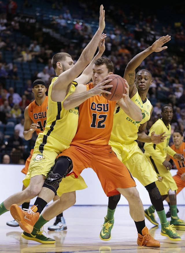 Oregon State's Angus Brandt (12) drives against Oregon's Ben Carter, left, and Elgin Cook in the first half of an NCAA college basketball game in the Pac-12 men's tournament Wednesday, March 12, 2014, in Las Vegas. (AP Photo/Julie Jacobson)