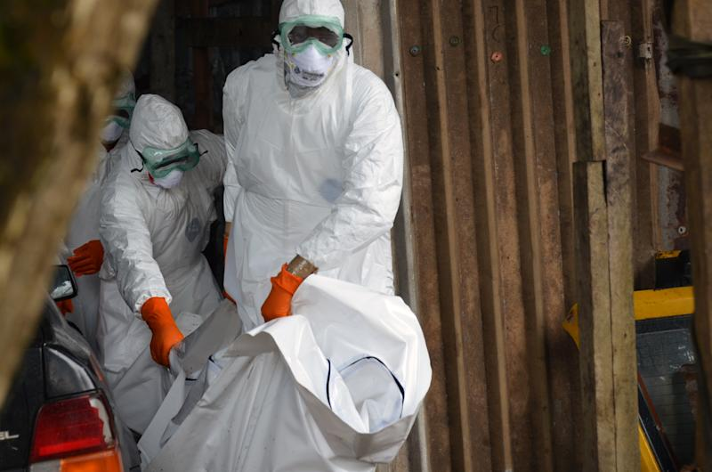 Liberian Red Cross health workers wearing protective suits carry the body of a victim of the Ebola virus on September 10, 2014 in a district of Monrovia