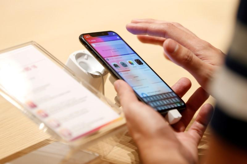A customer tests the features of the newly launched iPhone X at VIVA telecommunication store in Manama